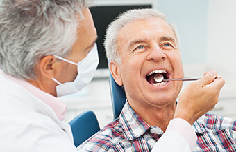 Older male patient examined by dentist