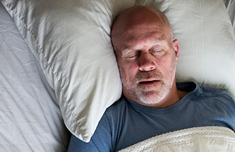 Man sleeping deeply in comfortable bed