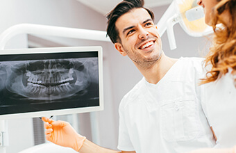 Dentist and patient examine digital x-rays