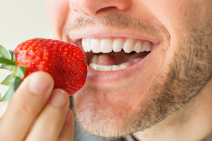 man eating strawberry