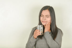 Woman with sensitive teeth holding glass of water